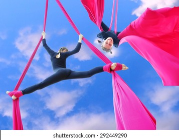 Outdoor activity of cheerful child training on aerial silks or ribbons in the sky.  Childhood, sports, active lifestyle concept.
