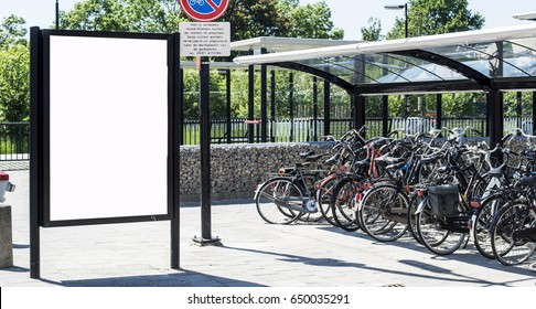Outdoor advertising abri or billboard at station with bicycles