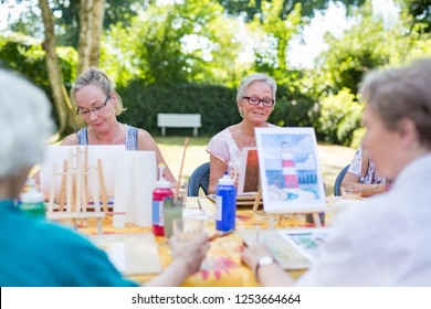 Outdoor art lesson in the park, ladies sitting at the table and learning to paint pictures.