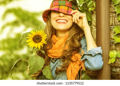 Outdoor atmospheric lifestyle photo of lovely woman wearing hat and orange scarf. Brown curly hair. Warm autumn colors. Season image