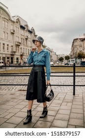 Outdoor autumn fashion portrait of elegant, luxury lady wearing trendy bucket hat, black faux leather midi skirt, blue denim shirt, cowboy ankle boots, holding small baguette bag, walking in street