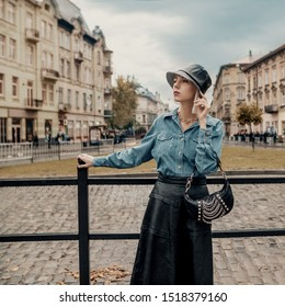 Outdoor autumn fashion portrait of elegant, luxury lady wearing trendy faux leather bucket hat, black midi skirt, denim shirt, holding small baguette bag with chains, posing in street of European city
