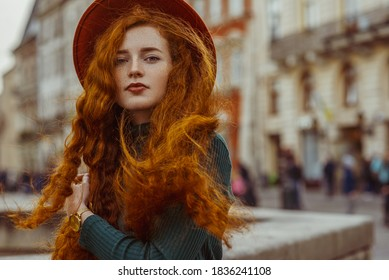 Outdoor autumn fashion portrait of elegant redhead freckled woman with long curly hair, wearing orange hat, green turtleneck, wrist watch, posing in street of European city. Copy, empty space for text
