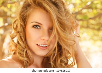 Outdoor autumn portrait of beautiful happy young woman