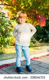 Outdoor autumn portrait of a cute little boy of 4 years old on a nice sunny day, wearing beige top, light blue denim jeans and boots