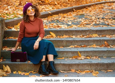 Outdoor autumn portrait of happy smiling lady wearing wrist watch,  beret, orange glasses, turtleneck, blue skirt, black chunky ankle boots, with quilted purple bag, sitting on stairs. Copy space