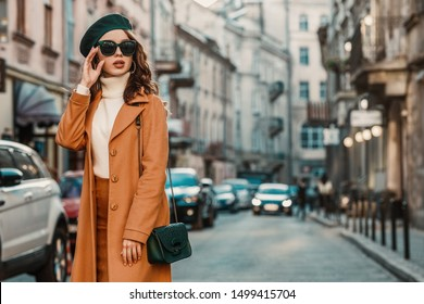 Outdoor autumn portrait of young elegant fashionable woman wearing trendy sunglasses, camel color coat, turtleneck, with textured leather shoulder bag, walking in street of European city. Copy space