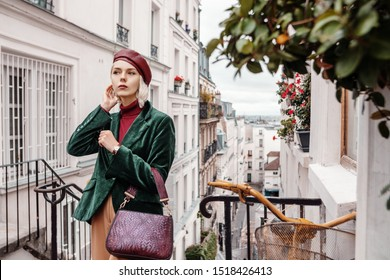 Outdoor autumn portrait of young fashionable lady wearing trendy dark red faux leather beret, turtleneck, green velour blazer, wrist watch, holding textured bag, posing in street of Paris. Copy space