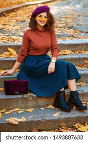 Outdoor autumn portrait of young happy smiling curly lady wearing wrist watch,  beret, orange glasses, turtleneck, blue skirt, black chunky ankle boots, with quilted purple bag, sitting on stairs