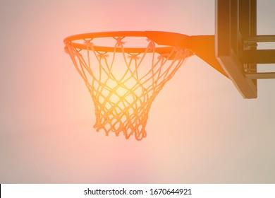Outdoor basketball hoop, sun in the net, toned