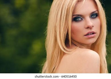 Outdoor blonde girl closeup portrait in a park.