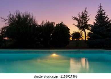 Outdoor blue liner swimming pool with lighting at dusk twilight sunset on a clear evening of summer, France.