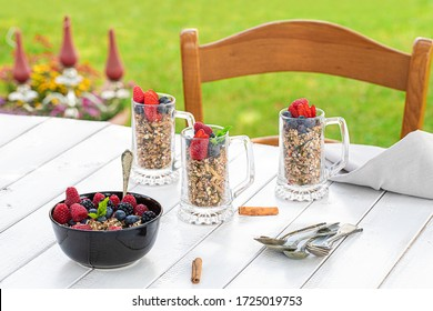 Outdoor breakfast with cereals and berries on white table and green lawn.