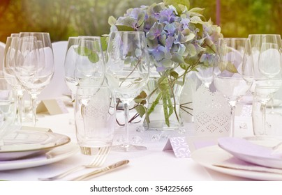 Outdoor bright wedding day - white table setting with empty glasses, white plates and fresh blue flowers