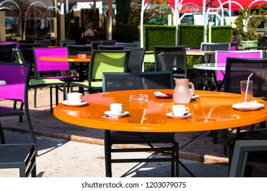 Outdoor Cafe with Empty Table, chairs and used coffee cups