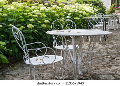 Outdoor cafe in the French Countryside with white tables and chairs