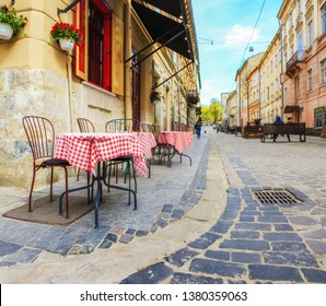 Outdoor cafe in the old town. Summer cafe in the narrow old street.  Vintage tables on narrow paved  street among houses and between walls in Lviv, Ukraine. Concept  - travel, landmarks