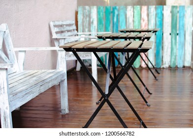 outdoor cafe tables. coffee house interior. wooden bench and table on the background of boards. street cafe