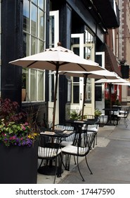 Outdoor cafe tables with umbrellas up and places set waiting for customers to arrive