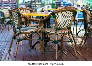 outdoor cafe, yellow tables, wicker chairs, wooden floor