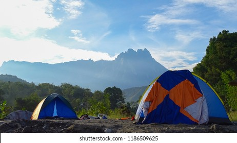 Outdoor camping scenery with sunny day and background of mount Kinabalu in Melangkap river,Kota Belud,Sabah Borneo,Malaysia.Tourists camped in the woods on the shore of the river on the hillside.