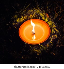 Outdoor candle burning in the grass