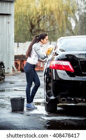 outdoor car wash with yellow sponge. Beautiful girl washes the car