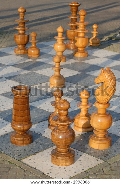 outdoor chess game with big wooden pawns