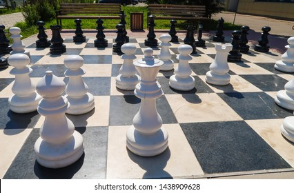Outdoor chessboard with large wooden figures. Outdoor giant chess in the public area, Close up large pieces of street chess in the park.
