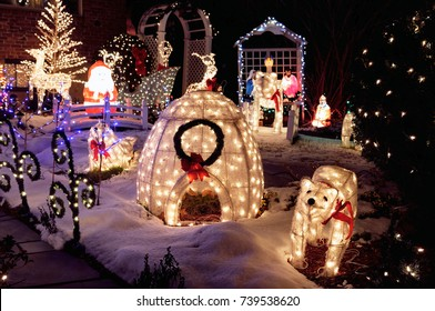 Outdoor Christmas decoration. Lights and lighted ornaments glowing in the night, house yard covered with snow.