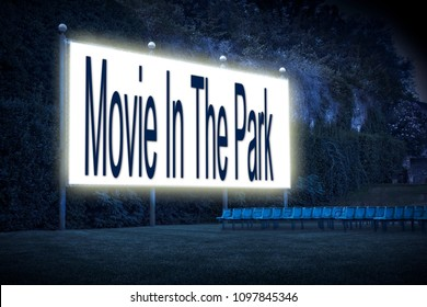 Outdoor cinema with chairs and white projection screen with 'Movie In The Park' text written on it