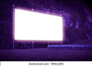Outdoor cinema with chairs and white projection screen in nature - Toned image with copy space