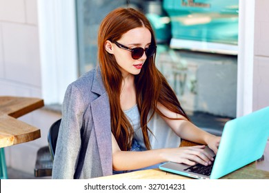 Outdoor city fashion portrait of young businesswoman working at cafe on terrace at sunny day, casual stylish outfit, mint details, using her laptop, cafe break, business concept.