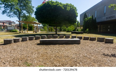 outdoor classroom on sunny day on school grounds amphitheatre stage wood logs tree neighborhood canada
