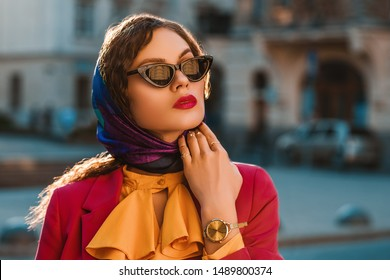 Outdoor close up fashion portrait of elegant lady wearing trendy colorful head scarf, black cat eye sunglasses, golden wrist watch, posing in street of city. Copy, empty space for text