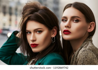 Outdoor close up fashion portrait of two young beautiful women with red lips makeup, wearing trendy clothes and accessories,  posing in street of european city