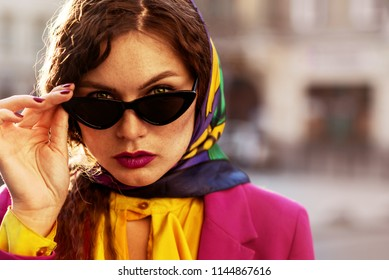 Outdoor close up fashion portrait of young beautiful woman with freckles,  wearing trendy cat eye black sunglasses, colorful kerchief, posing in street of city. Copy, empty space for text
