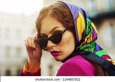 Outdoor close up fashion portrait of young beautiful woman with freckles, pink fuchsia lips, wearing trendy cat eye black sunglasses, colorful kerchief, posing in street of city. Copy space for text