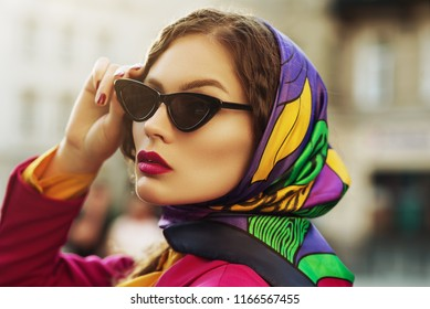 Outdoor close up fashion portrait of young beautiful woman with pink fuchsia lips, wearing trendy cat eye black sunglasses, colorful kerchief, posing in street of city