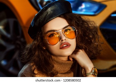 Outdoor close up fashion portrait of young beautiful confident woman wearing stylish orange aviator sunglasses, leather beret, cashmere turtleneck,  wrist watch, posing in street, near the bright car