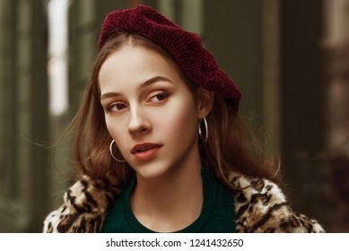 Outdoor close up fashion portrait of young beautiful confident woman wearing marsala color beret, silvery hoop earrings, leopard print coat, posing in street of european city