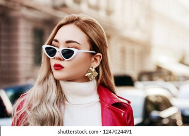 Outdoor close up fashion portrait of young beautiful fashionable woman with long blond hair, red lips, wearing stylish cat eye sunglasses, white turtleneck, jacket, posing in street. Copy, empty space