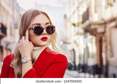 Outdoor close up fashion portrait of young beautiful fashionable woman wearing stylish turtle frame sunglasses, luxury wrist watch, red blazer, posing in street of european city. Copy, empty space