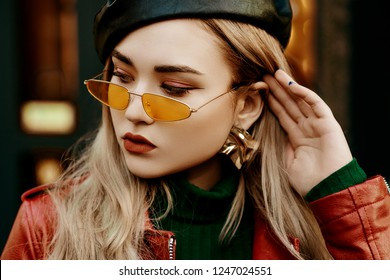Outdoor close up fashion portrait of young beautiful fashionable woman wearing stylish small orange sunglasses, leather beret, trendy earrings, red jacket, green turtleneck, posing in street of city