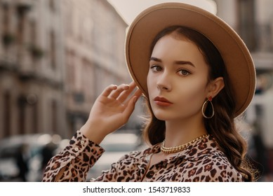 Outdoor close up fashion portrait of young elegant lady wearing beige fedora hat, trendy chain necklace, earrings, leopard print shirt, posing in street of European city. Copy, empty space for text