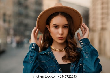 Outdoor close up fashion portrait of young elegant lady wearing beige fedora hat, trendy chain necklace, blue denim shirt, posing in street of European city. Copy, empty space for text