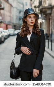 Outdoor close up fashion portrait of young elegant brunette woman wearing faux leather bucket hat, black suit, holding patent leather hobo handbag, posing, walking in street of European city.