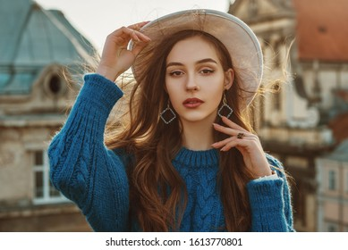 Outdoor close up fashion portrait of young elegant fashionable brunette woman, model wearing trendy blue sweater, stylish white hat, wrist watch, earrings, ring, posing at sunset, in European city