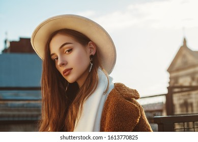 Outdoor close up fashion portrait of young elegant fashionable woman, model wearing stylish white hat, scarf, brown faux fur coat, posing at sunset, in European city. Copy empty space for text