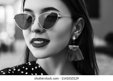 Outdoor close up monochrome portrait of young beautiful stylish woman wearing cat eye sunglasses, tassel earrings, posing in street. Female fashion concept